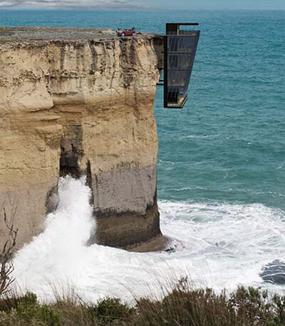 a view of cliff house above open water, hanging off the cliff's edge
