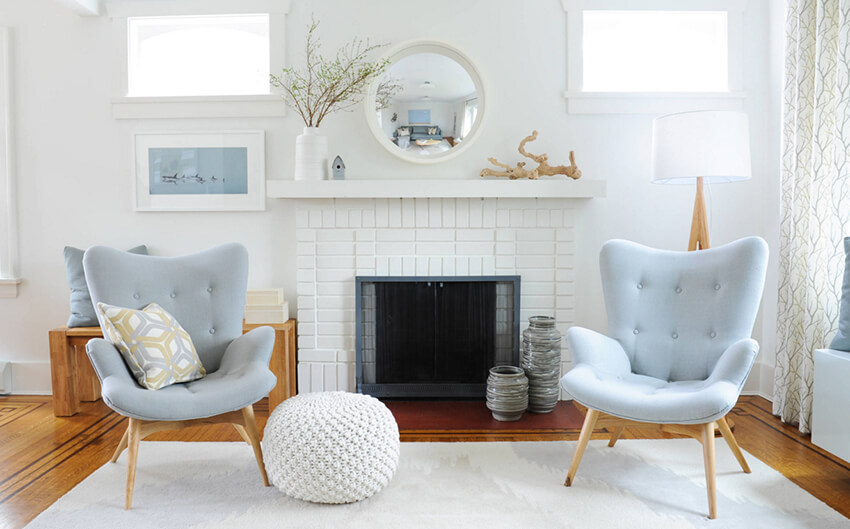 A room with two blue colored sofas, a soft white carpet on the ground, a Swedish Fireplace