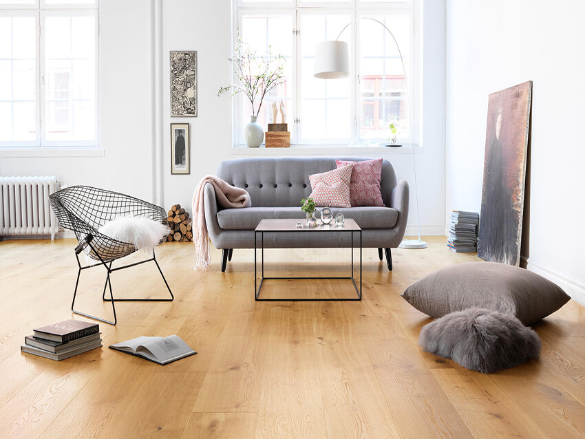 the Scandinavian interior design in a room uses a Sled base steel chair, a steel table and a gray sofa on the wooden flooring