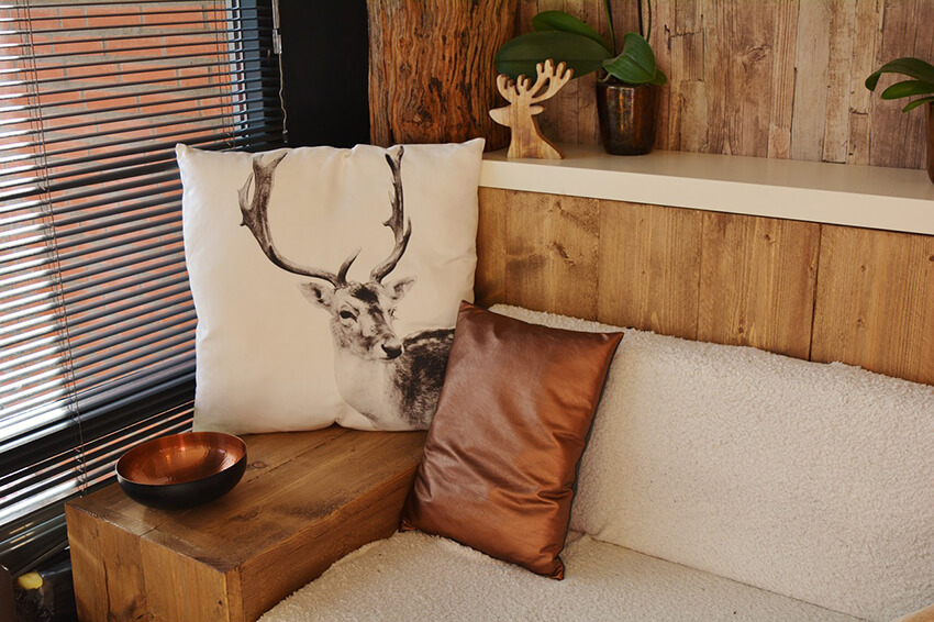 A wooden sofa with animal Print decorative cushions