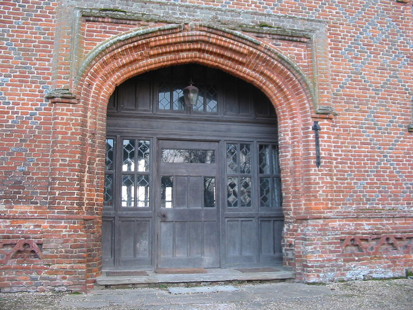 A brick wrought entrance of an ancient Tudor architecture building