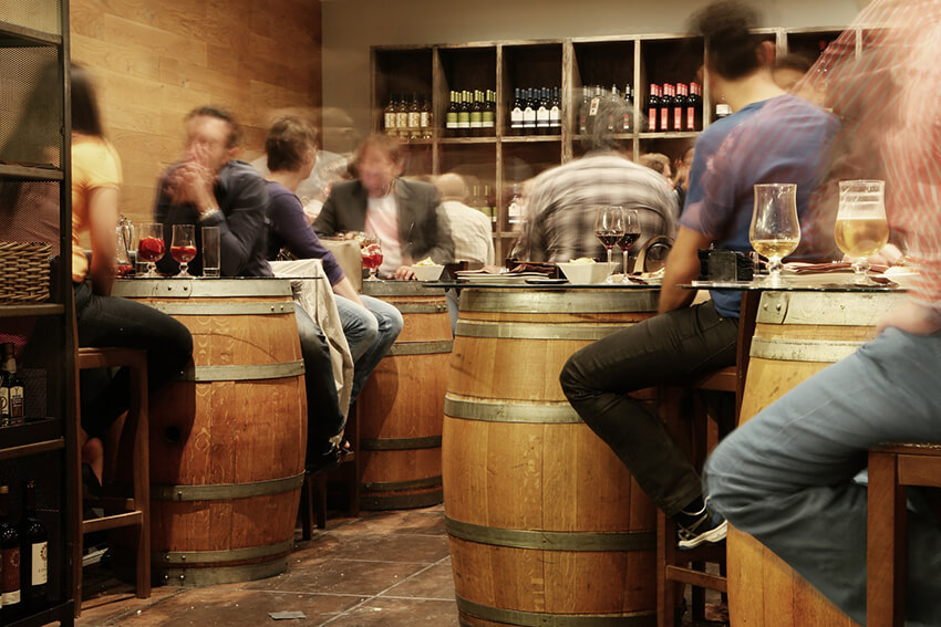 A busy bustling cask-themed bar with wooden barrel tables