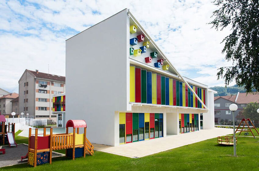 a green playground and a kindergarten building with a colorful facade