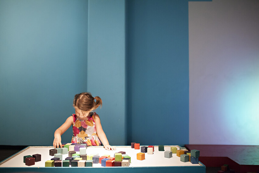A little girl playing Lego in a kindergarten with blue walls